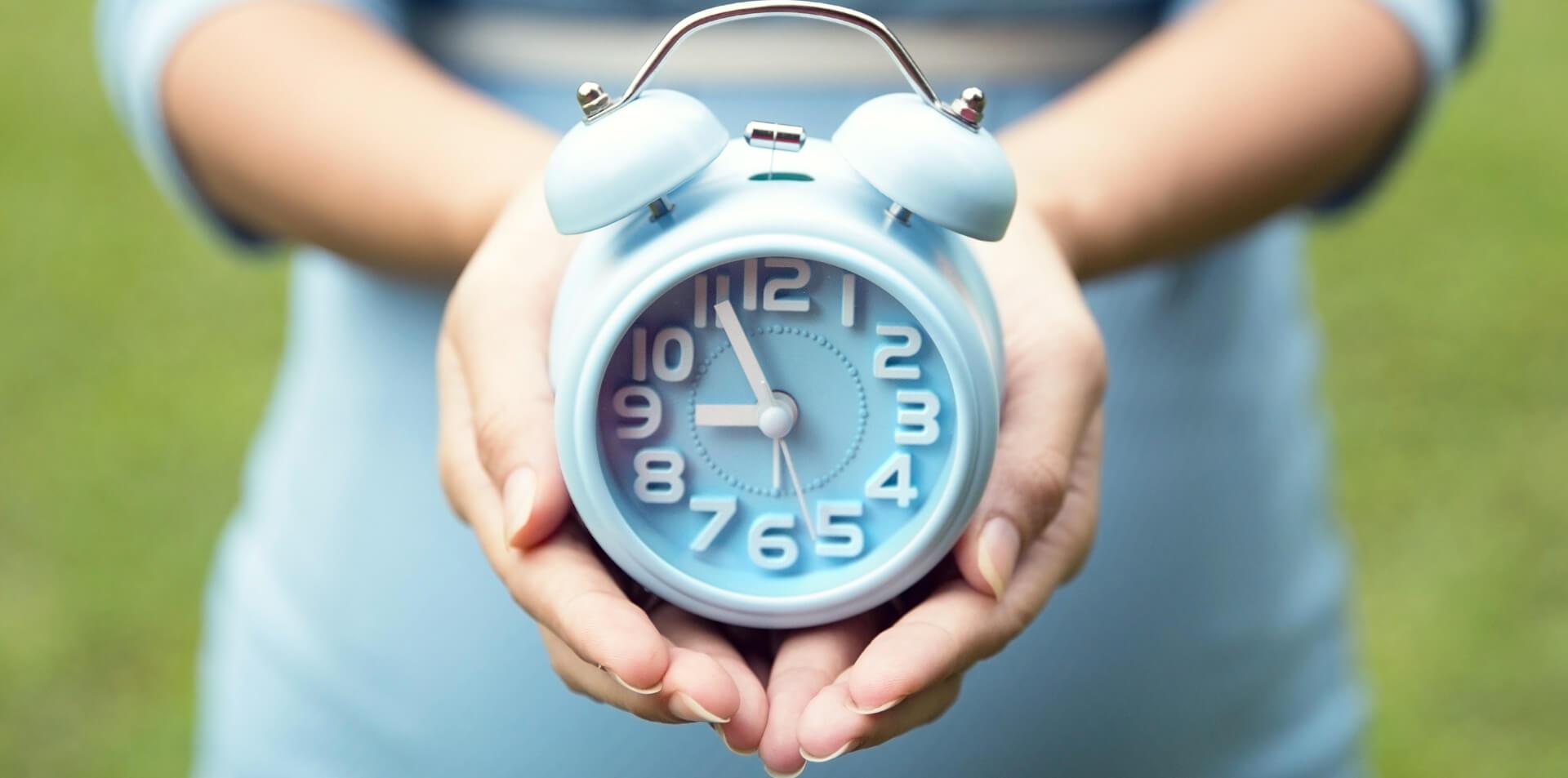 congelamento óvulos: mulher segurando um relógio