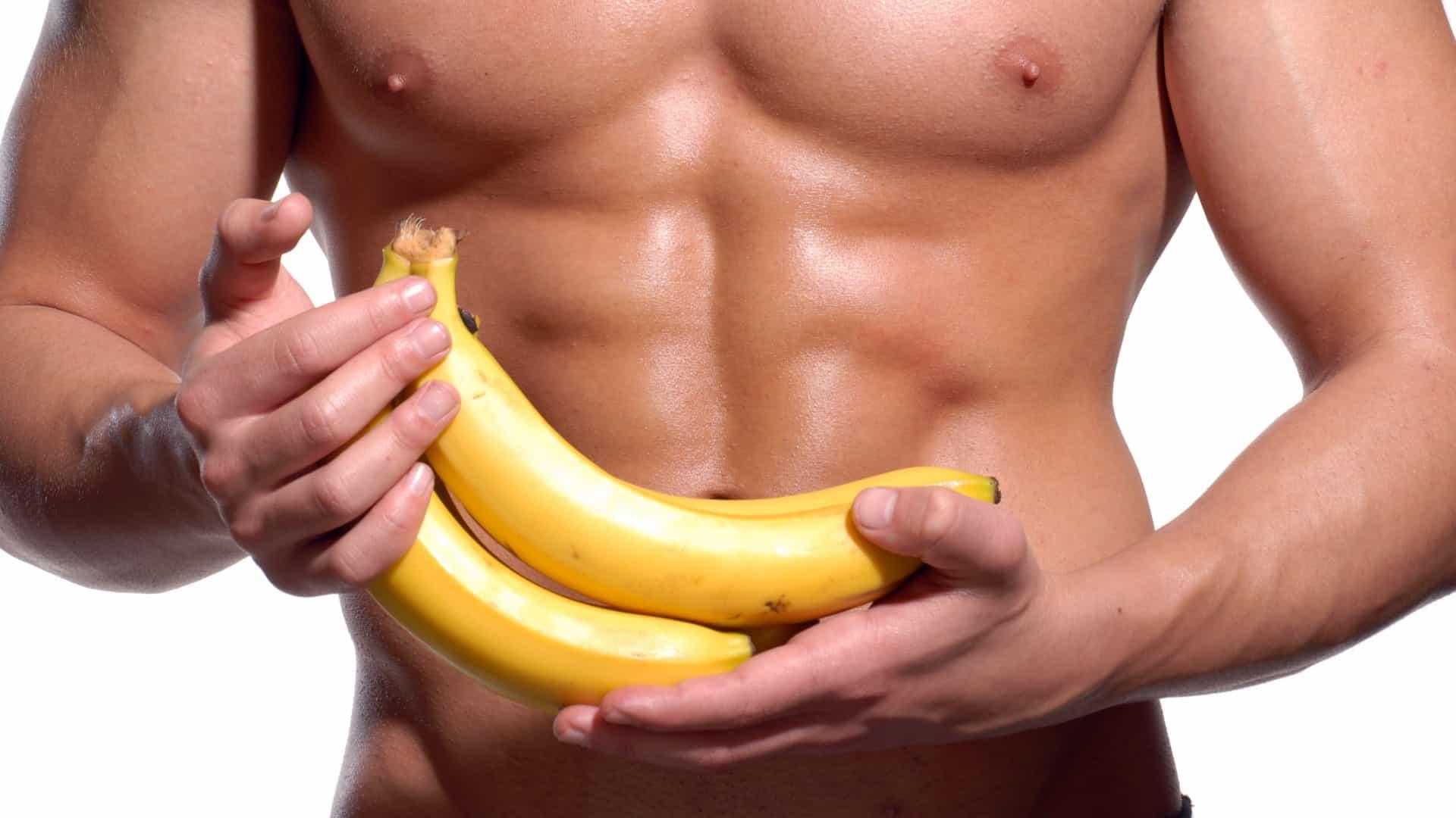 homem musculoso segruando bananas que ajudam a aumentar a quantidade de esperma