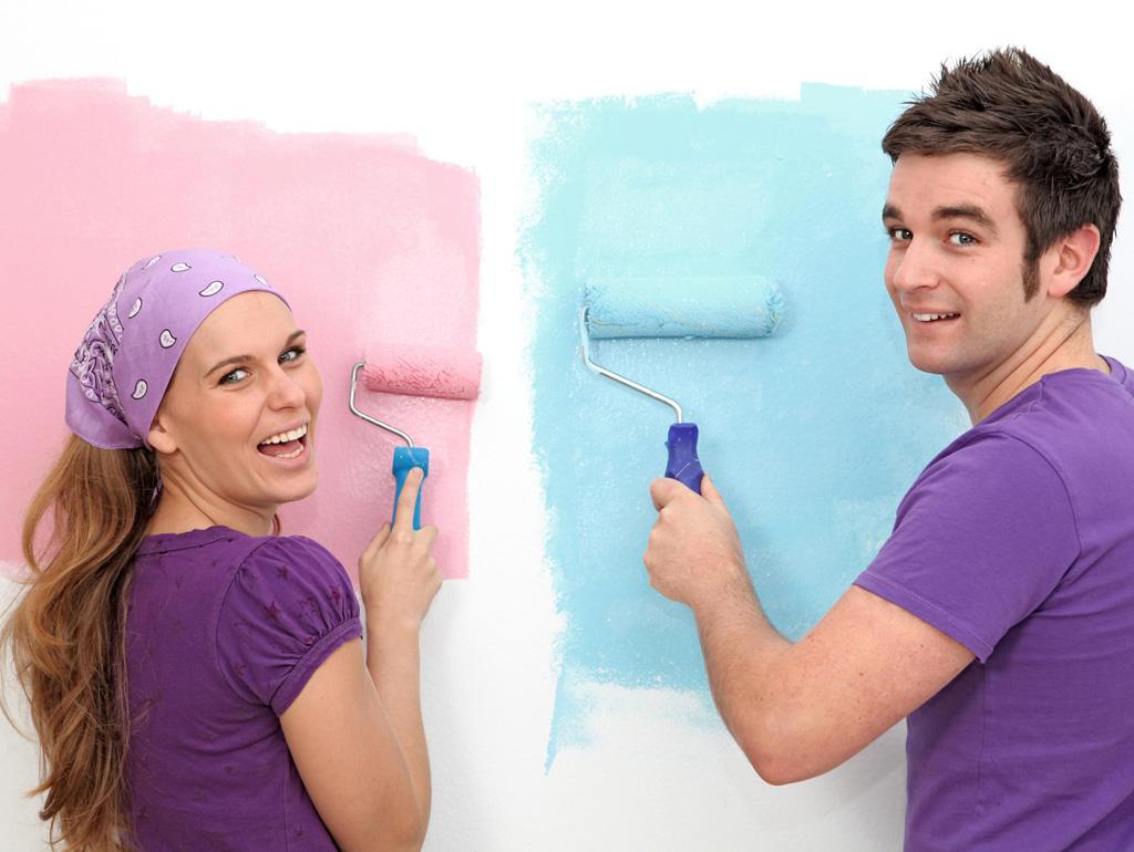 casal lintando aparede ocm rolo de tinta, ela rosa, ele azul