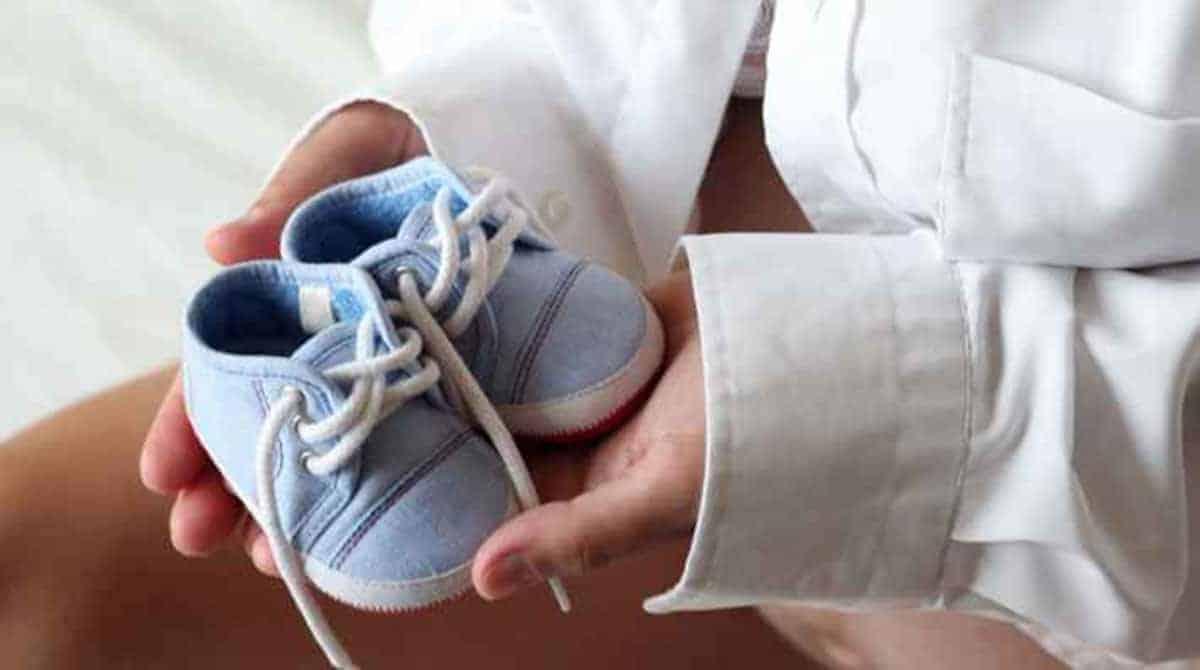 mulher sentada segurando sapatinhos de bebê azuis na mão