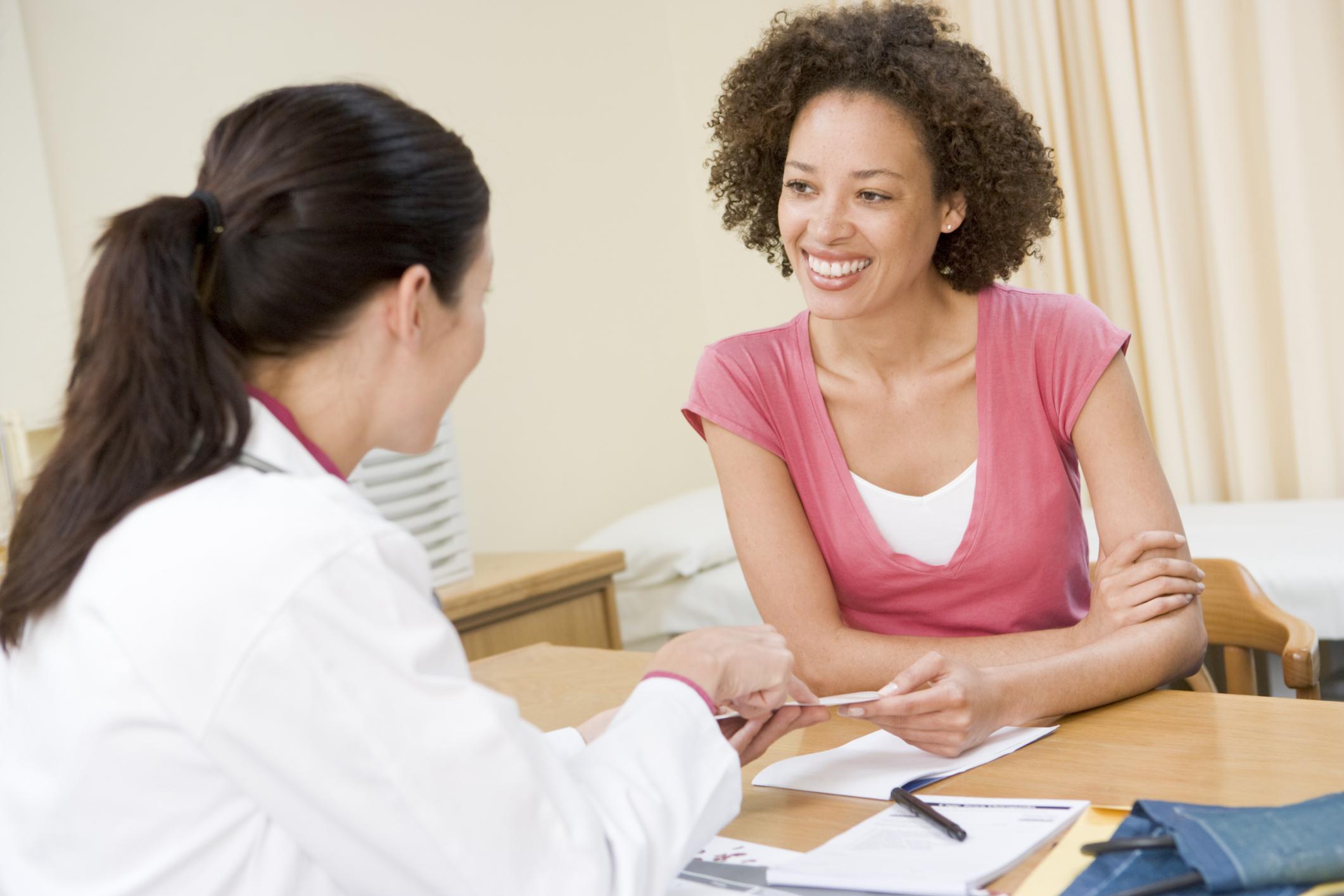 mulher em consultório médico conversando com médica