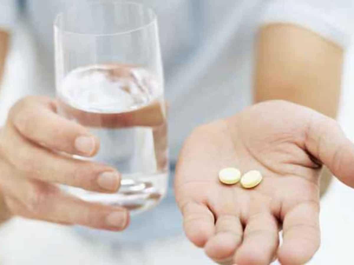 mulher com um copo de água na mão e 2 comprimidos na outra