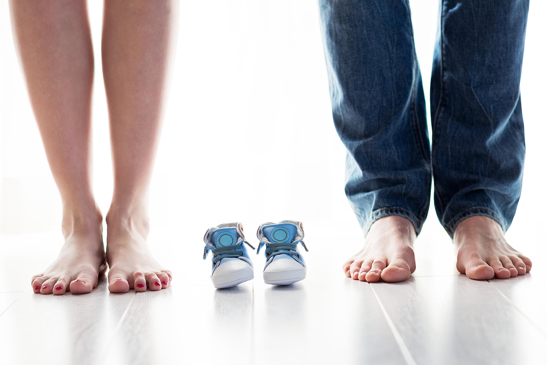 mulher e homem lado a lado com sapatinho de bebê entre as pernas