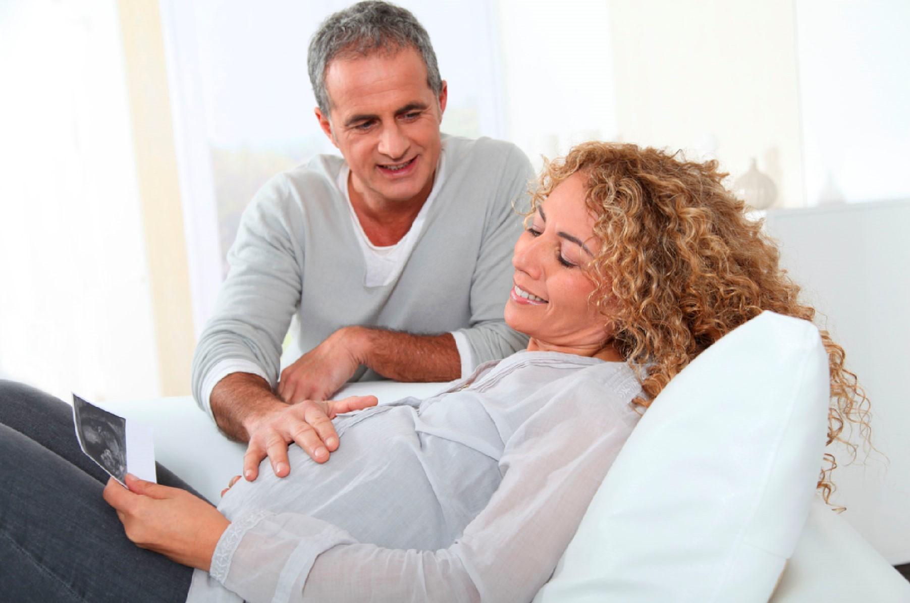 mulher grávida sentada no sifá com exame de ultrassom na mão e marido inclinado sobre ela com a mão na barriga dela