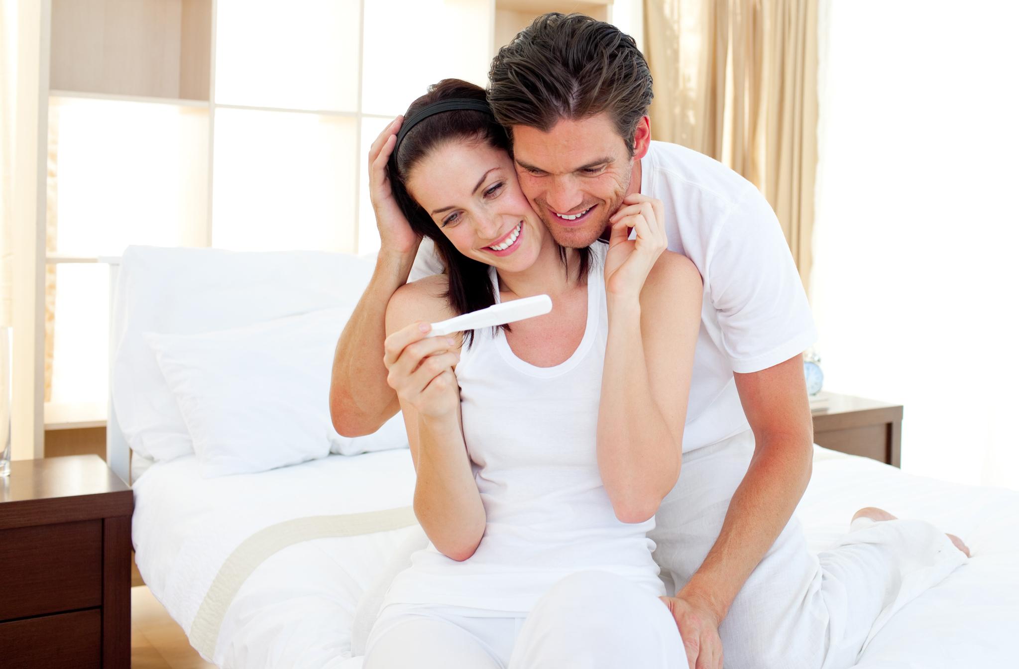 casal feliz com resultado de exame de gravidez após ter tido dificuldade para engravidar do segundo filho